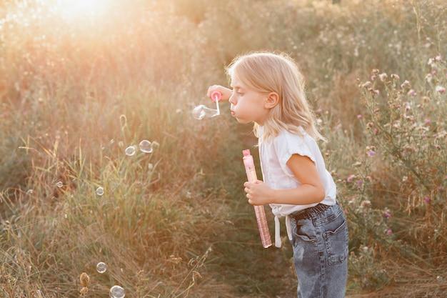 Een klein meisje met zeepbellen in de avond op een wandeling. mooi hoor