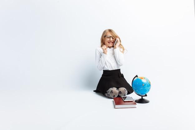 Een klein meisje, naar het beeld van een leraar, draagt een bril met een wereldbol en boeken, praat aan de telefoon en verheugt zich en lacht, vrolijk en lief