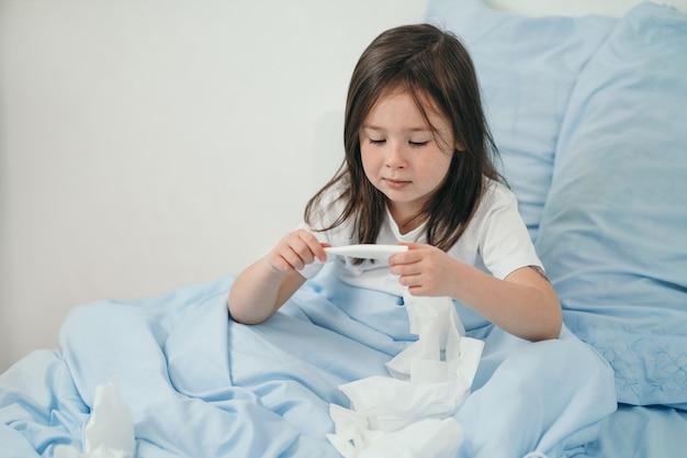 Een klein meisje neemt haar temperatuur op. het kind is verkouden en wordt thuis behandeld. bedrust voor verkoudheid. seizoensgebonden verkoudheid bij kinderen