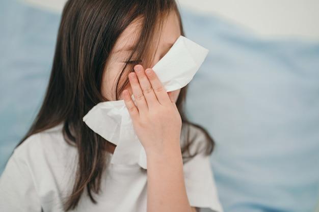 Een klein meisje niest. het kind is verkouden en wordt thuis behandeld. het meisje ligt in een bed met blauw beddengoed.