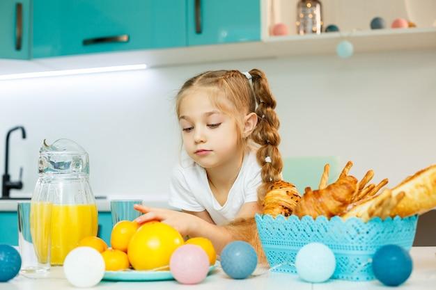 Een klein meisje ontbijt in de keuken met croissants en jus d'orange.