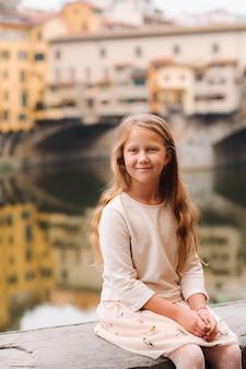 Een klein meisje op de achtergrond van de ponte vecchio-brug in florence.familiewandeling van de familie in italy.toscane.