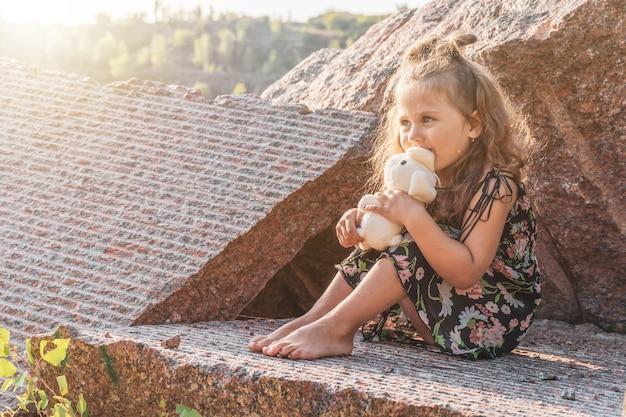 Een klein meisje op de rotsen met een speeltje in haar handen, de zon verlicht haar