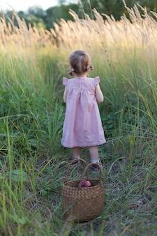 Een klein meisje op de weg in een tarweveld bij zonsondergang, lopend langs het pad met haar rug naar de camera, gaat in de verte.