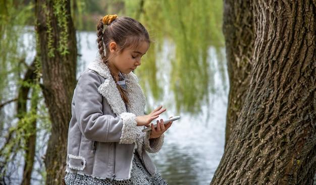 Een klein meisje, op een wandeling, met een telefoon in haar handen, besteedt geen aandacht aan de schoonheid van de natuur.