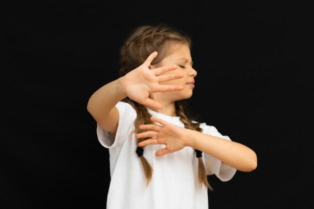 Een klein meisje op een zwarte achtergrond strekt zich uit haar handen.
