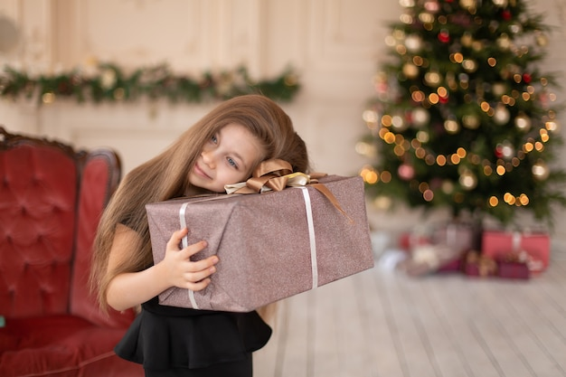 Een klein meisje opent een kerstcadeau van de kerstman. kerstverhaal. gelukkige jeugd.