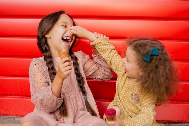 Een klein meisje pakt een ander bij de neus en lacht. ga bij het rode hek zitten