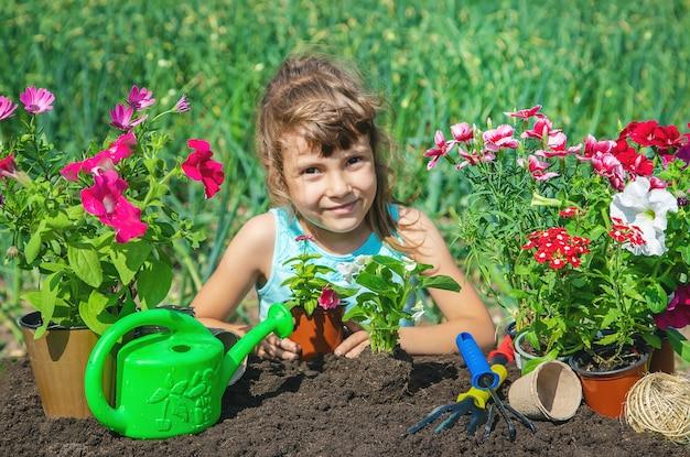 Een klein meisje plant bloemen.