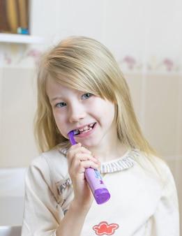 Een klein meisje poetst haar tanden met een elektrische tandenborstel.