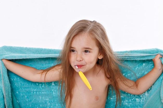 Een klein meisje poetst haar tanden op een witte achtergrond. portret van een kind met een gele tandenborstel. blauwe handdoek om haar nek. ochtend hygiëneprocedures