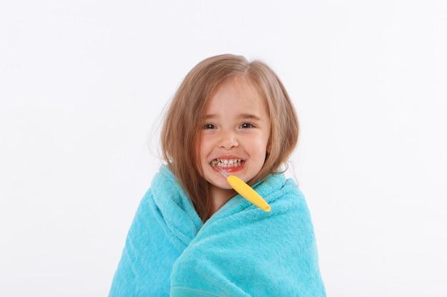 Een klein meisje poetst haar tanden op een witte achtergrond. portret van een kind met een gele tandenborstel. blauwe handdoek om haar nek.