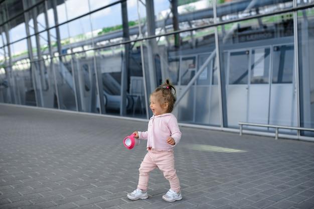 Een klein meisje probeert alleen te lopen in een modern gebouw