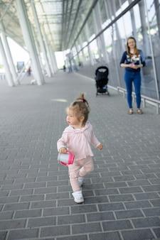Een klein meisje probeert in haar eentje een modern gebouw te lopen. in de hand van een meisje met een kopje morsen.