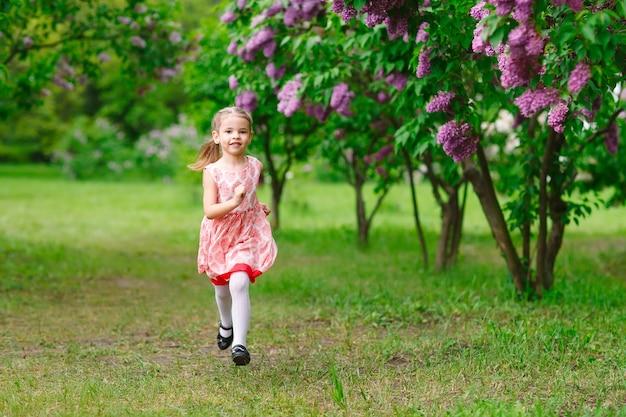 Een klein meisje rent in het park.