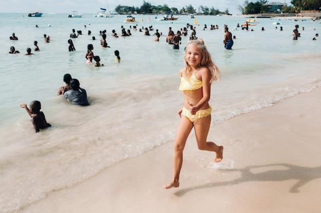 Een klein meisje rent langs een tropisch strand met de lokale bevolking op het eiland mauritius. een meisje op het strand van de indische oceaan en onherkenbare lokale bevolking van het eiland mauritius.