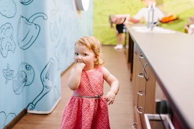 Een klein meisje rent, loopt weg van haar moeder en speelt in de keuken. gelukkige kinderen.