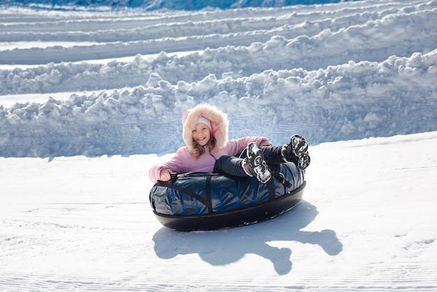 Een klein meisje rijdt met een buis van een glijbaan