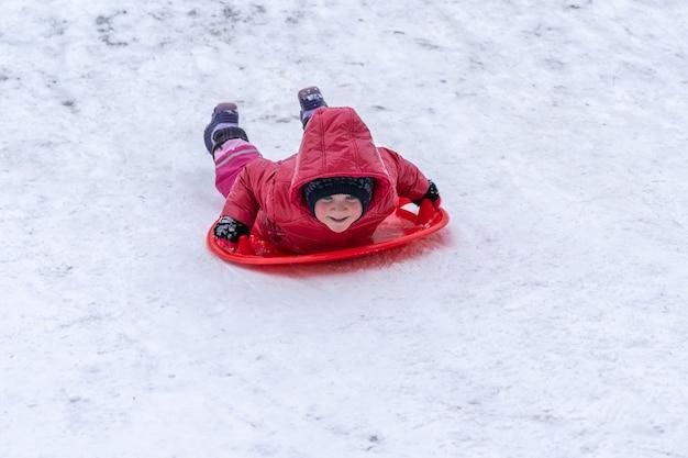 Een klein meisje rijdt op een slee van een winterglijbaan. kerstvakantie.