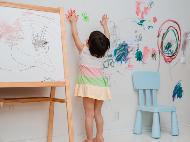 Een klein meisje schilderde een gebogen blik met verf en een borstel op de muur van haar kamer.