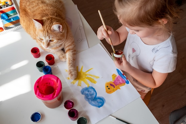 Een klein meisje schildert de zon en haar moeder met aquarellen
