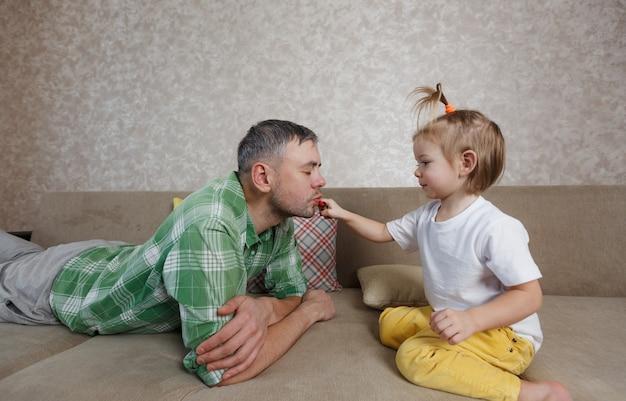 Een klein meisje schildert haar lippen met felle lippenstift aan haar vader