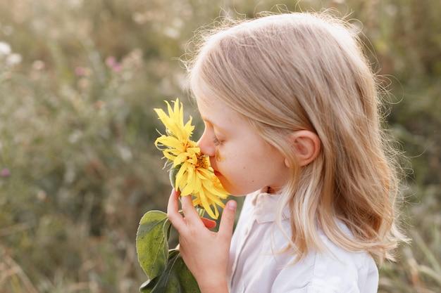 Een klein meisje snuift een gele bloem. detailopname