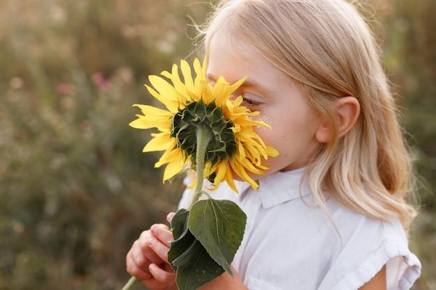 Een klein meisje snuift een zonnebloem. detailopname