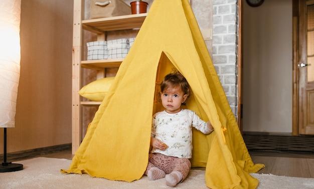 Een klein meisje speelt in een gele tipi