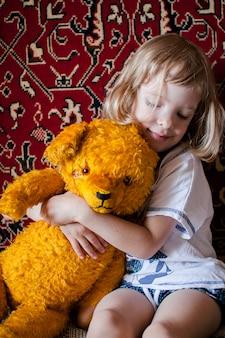 Een klein meisje speelt met een oude sovjet-speelgoedbeer