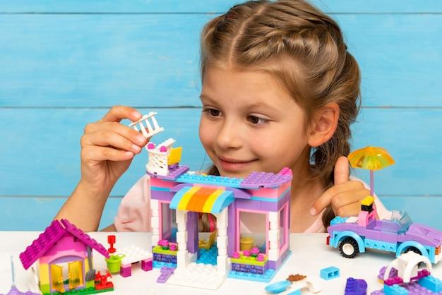 Een klein meisje speelt met gekleurde blokken