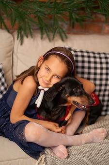 Een klein meisje speelt met haar hond in de buurt van de kerstboom.