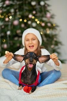 Een klein meisje speelt met haar hond in de buurt van de kerstboom