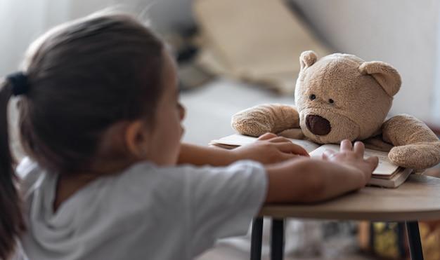Een klein meisje speelt met haar teddybeer en een boek, leert hem lezen, speelt op school.