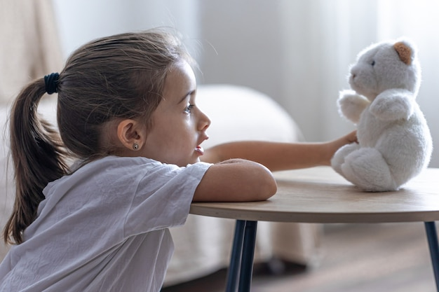 Een klein meisje speelt met haar teddybeer.