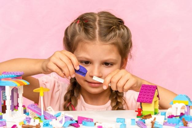 Een klein meisje speelt met plastic blokjes op een roze