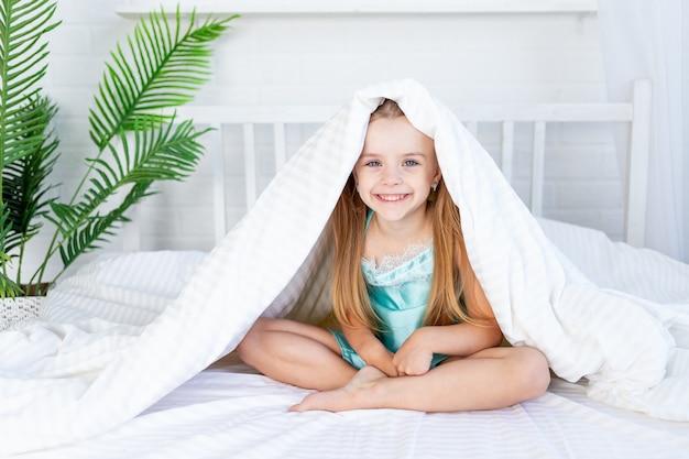 Een klein meisje speelt onder de deken en wordt 's ochtends thuis op het bed op een wit katoenen bed wakker en lacht lief