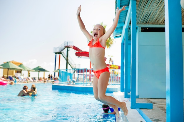 Een klein meisje springt tijdens de zomervakantie in het zwembad van het waterpark. Premium Foto