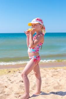 Een klein meisje staat bij de zee en eet maïs zomervakanties en plezier