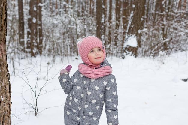 Een klein meisje staat in een besneeuwd bos en kijkt op. kinderspellen in het winterbos. familie wintervakantie met een kind.