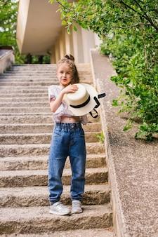 Een klein meisje staat in het park en houdt een hoed in haar handen. het kind is blij en lacht.
