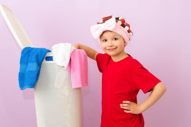 Een klein meisje staat naast een mand met vuile kleren in een rood t-shirt en met krulspelden op haar hoofd.