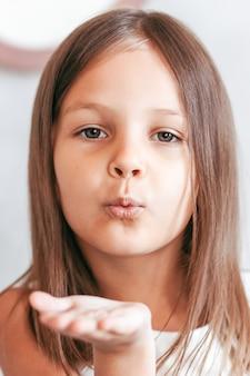 Een klein meisje stuurt een luchtkus. close-up portret