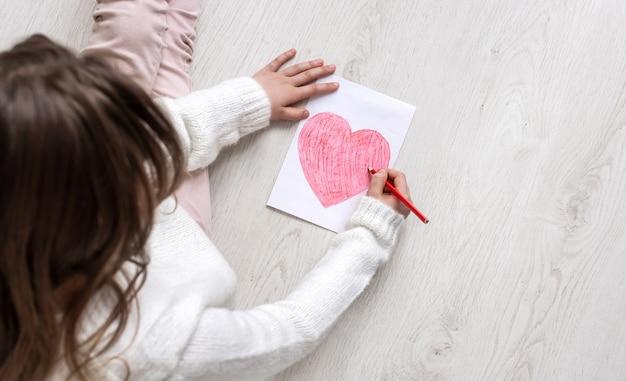 Een klein meisje tekent een hart op de grond