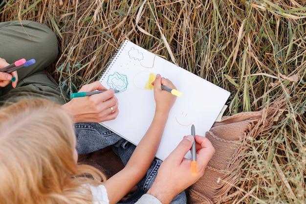 Een klein meisje tekent met haar ouders tijdens een picknick. detailopname