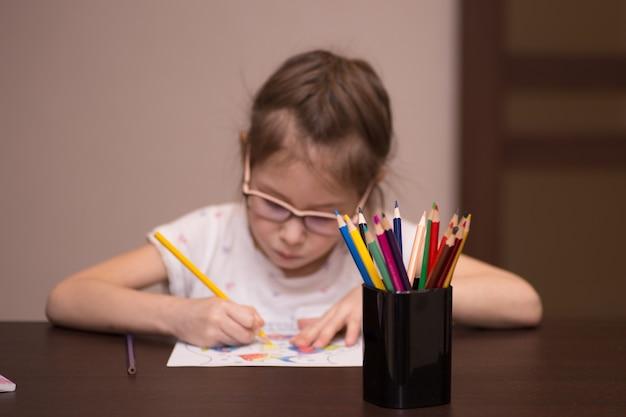 Een klein meisje tekent met kleurpotloden