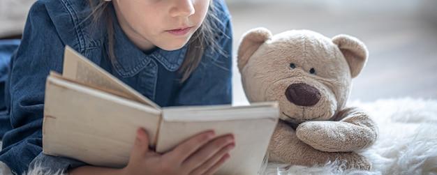 Een klein meisje thuis, liggend op de vloer met haar favoriete speeltje en leest een boek.