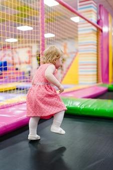 Een klein meisje van 1-2 jaar dat voor haar verjaardag op een trampoline speelt en springt in een kinderspeelkamer. uitgaanscentrum.