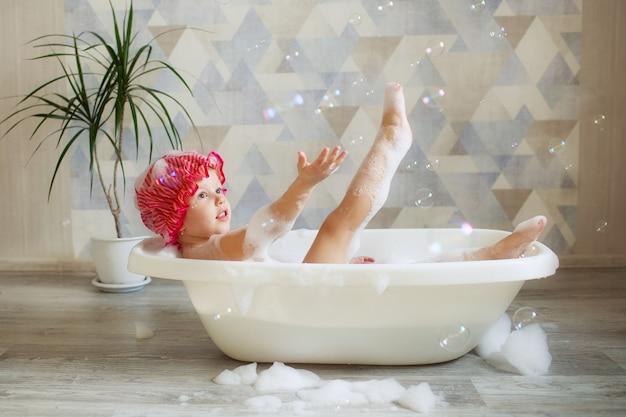 Een klein meisje van 3-4 jaar oud baadt in een mooie badkamer op een lichte muur. hygiëne voor kinderen.