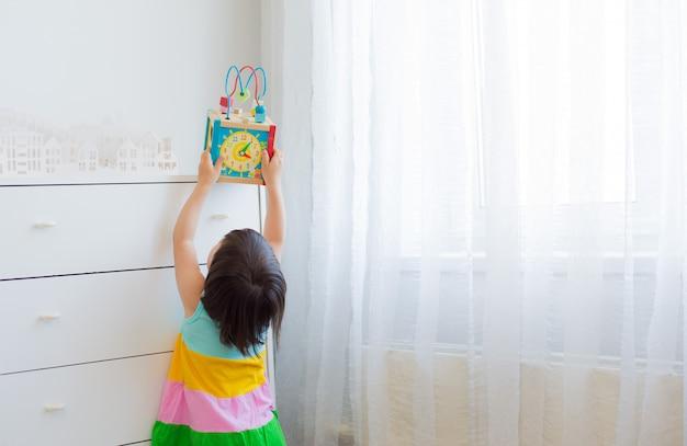 Een klein meisje van 3 jaar rekt zich uit om een educatief speelgoed van een hoge plank te krijgen.